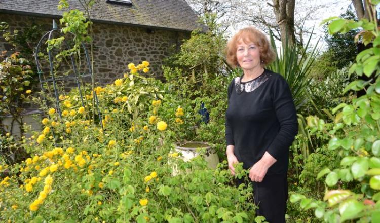 Lynn Chesters, dans son jardin qu'elle bichonne, à Martigné-sur-Mayenne. Le thé et le jardin restent anglais, mais la résidente installée depuis 2001 est fermement attachée à cette campagne mayennaise.